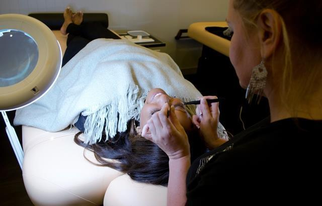 A technician applies eyelash extensions at the Lash Loft