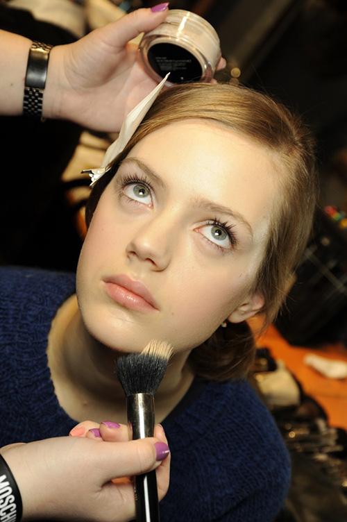 A makeup artist applies foundation to a model