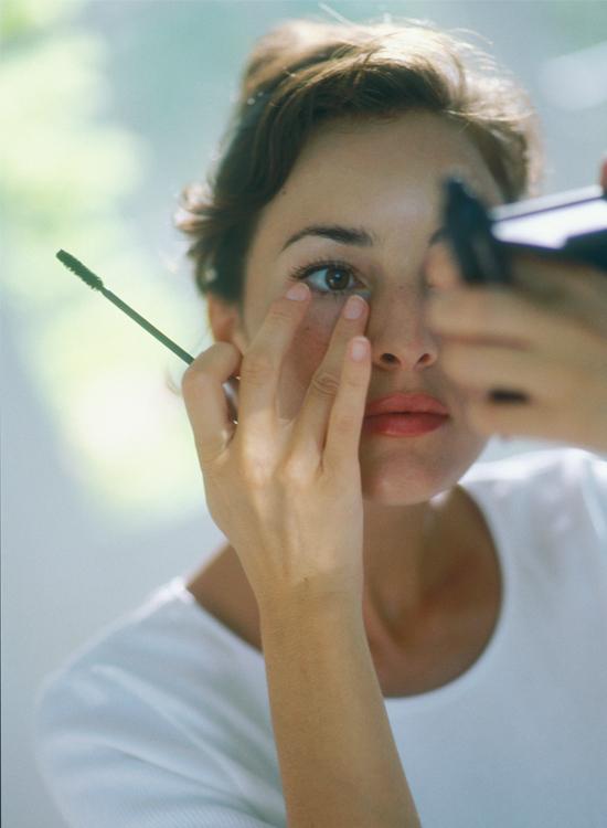 Woman applying mascara